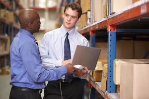 twee zakenlieden met laptop in magazijn