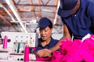voorman die jonge naaimachinist helpt foto
