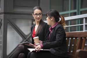 twee vrouwelijke ondernemers met digitale tablet in een moderne stedelijke omgeving. foto