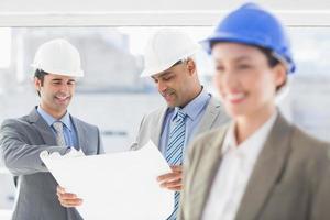 glimlachende architect met erachter team foto