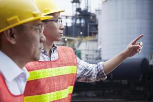 twee ingenieurs in beschermende werkkleding die buiten een fabriek wijzen foto