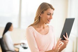 gelukkig zakenvrouw kijken naar touchpad in kantoor foto