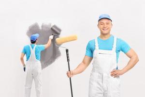 twee mannelijke schilders schilderen een muur foto