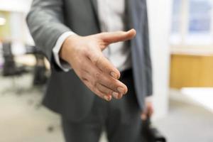 zakenman die een hand in bureau geeft foto