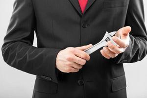 zakenman die een moersleutel houdt
