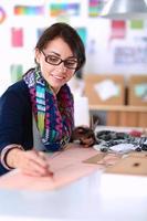 naaister ontwerpen van kleding patroon op papier foto