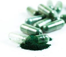 groene kruidengeneeskunde capsule geïsoleerd op een witte achtergrond foto