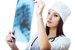 vrouwelijke arts die een röntgenstraal bekijkt, die op wit wordt geïsoleerd foto