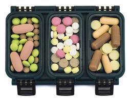 multi-coloured pillen in groene doosorganisator die op wit wordt geïsoleerd foto