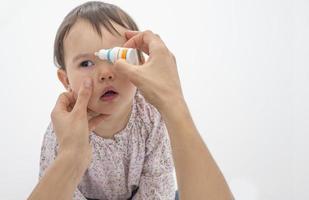 moeder gieten oogdruppels in het oog van haar dochter foto