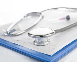 medische geschiedenis op klembord met stethoscoop op lichte pagina foto