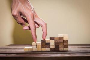 de hand vergelijkt bedrijfspersoon die een stuk speelgoed trap opvoert foto