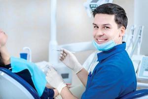 succesvolle artsentandarts. glimlachende tandarts controleert de tanden van t foto
