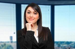 Glimlachende zakenvrouw in het kantoor foto