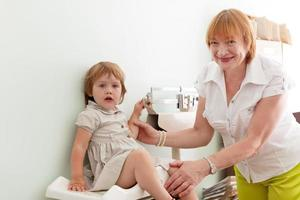 kinderarts weegt de baby foto