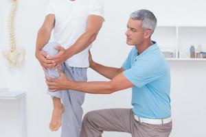 arts die zijn geduldige benen onderzoekt foto