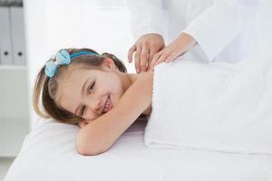 klein lachend meisje liggend op een tafel foto