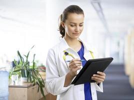 mooie vrouwelijke arts die de patiëntengrafiek onderzoekt foto