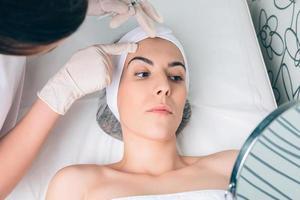 vrouwelijke arts die de gezichtszones voor patiënt toont foto