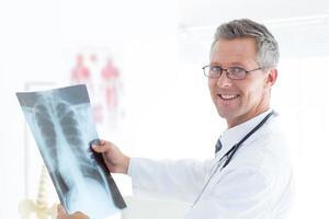 glimlachende arts die xray houdt foto