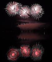 kleurrijk vuurwerk met reflectie op meer. foto