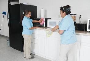 twee dienstmeisjes die een bedrijfsonderbrekingsruimte schoonmaken foto