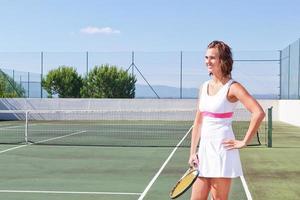 mooi jong meisje met een tennisracket klaar om uit te oefenen. foto