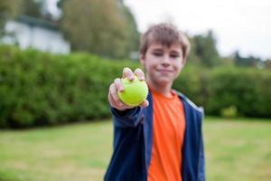 jongen met tennisbal foto