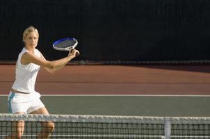 jonge vrouwelijke tennisser swingende racket op de rechtbank