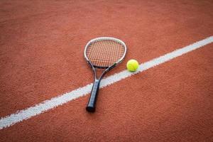 tennisracket en bal op de baan