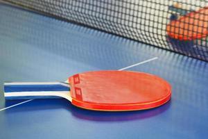 twee rode tennisracket op tafeltennistafel foto