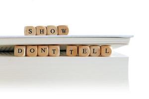 """wit boek of skript stack met bericht """"show don't tell"""" foto"""