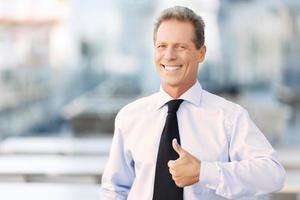 aardige zakenman die zich dichtbij bureaugebouw bevindt foto