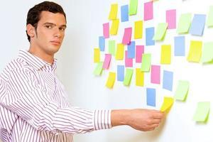 portret dat van zakenman kleverige nota's houdt foto