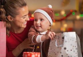 gelukkige moeder en baby het controleren van kerst boodschappentassen