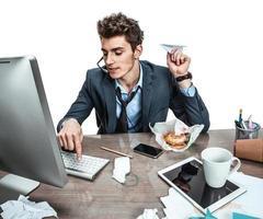jonge kantoor man met papieren vliegtuigje in zijn hand foto
