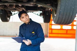 automonteur bezig met een auto in zijn garage foto