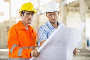 mannelijke architecten analyseren blauwdruk op de bouwplaats foto
