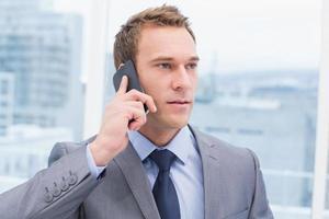 zakenman die mobiele telefoon in bureau met behulp van foto