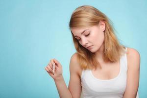 griep. ziek meisje met koorts thermometer controleren. foto