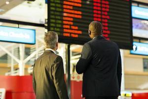 zakenlieden die vluchtinformatiebord bekijken foto