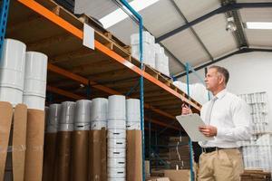 magazijnbeheerder die zijn lijst op klembord controleert