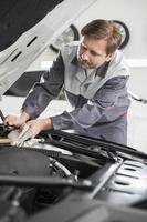 mannelijke monteur repareren van automotoren in werkplaats foto