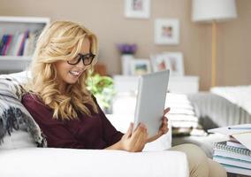 blonde jong meisje met digitale tablet thuis foto
