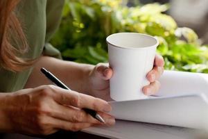 jonge vrouw aan het werk koffie drinken uit wegwerp beker. foto