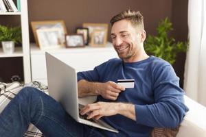 lachende man tijdens online winkelen thuis foto