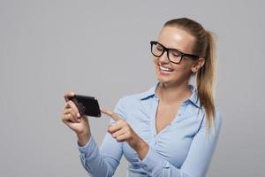 glimlachende vrouw met een bril met behulp van mobiele telefoon