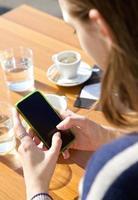 portret van achter van een jonge vrouw die SMS-bericht verzendt foto