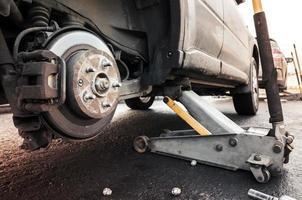 wielen van een auto vervangend, houdt krik het lichaam vast foto