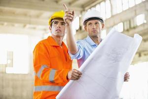 mannelijke architecten met blauwdruk werken op de bouwplaats foto
